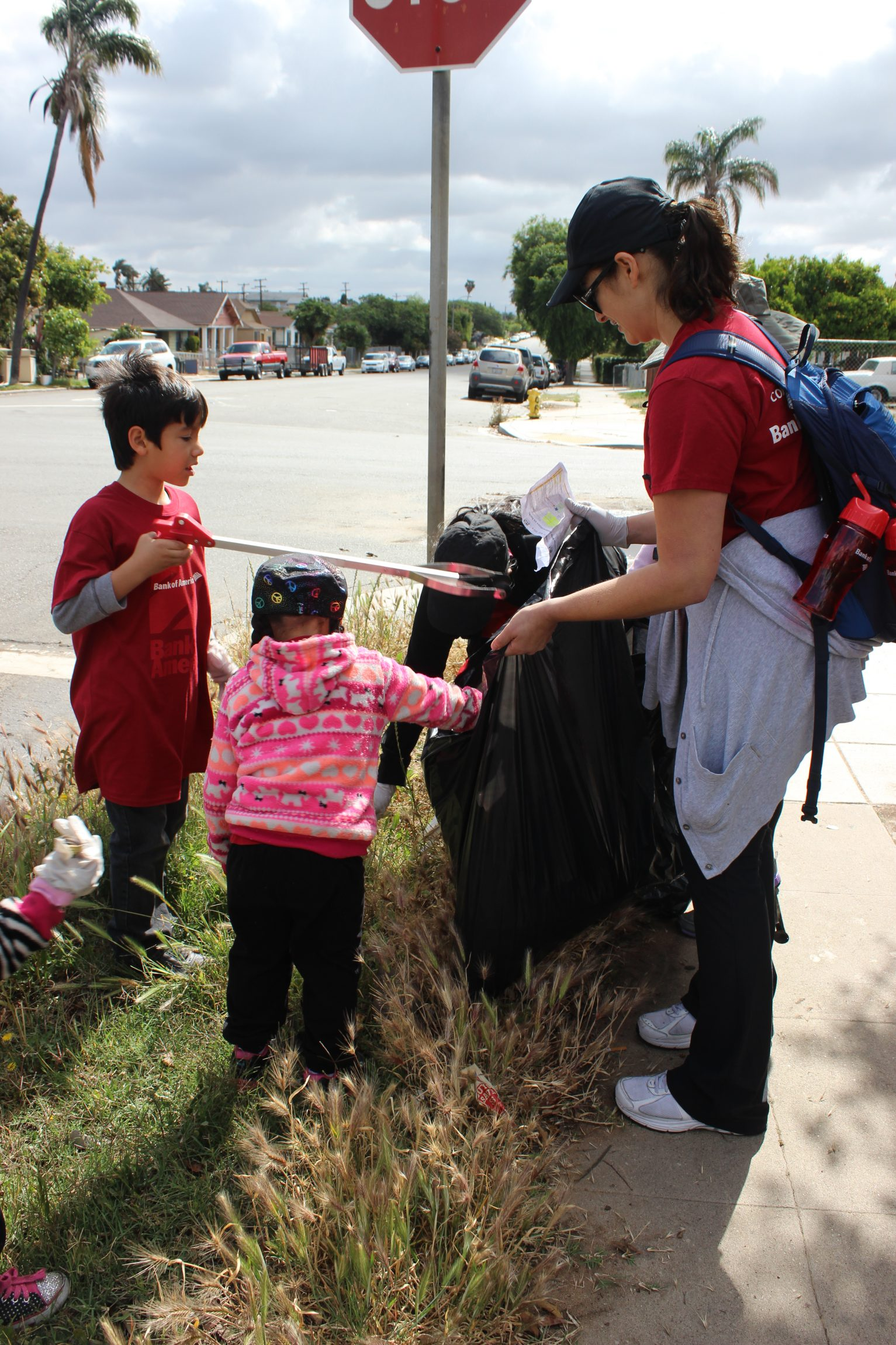 A family with the Bank of America volunteer team at Memorial Community Park works together to clean up Logan Heights.